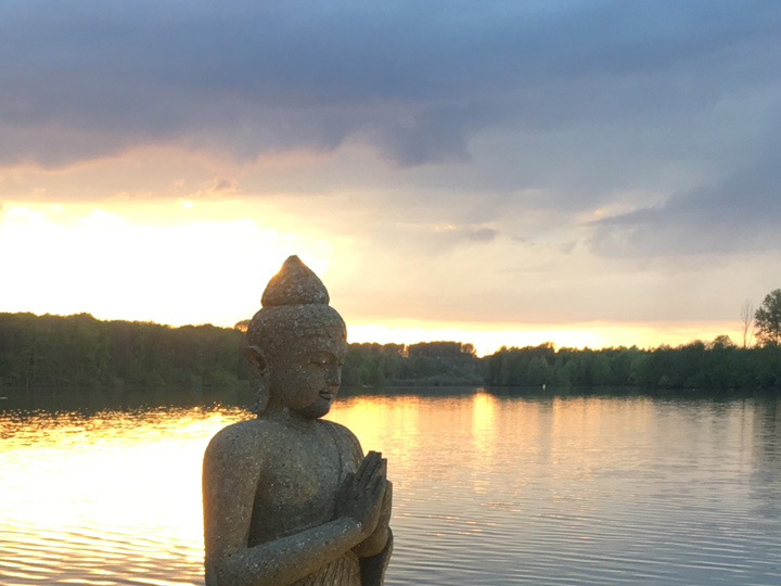 Blick in den Sonnenuntergang über den See mit Steinstatue im Vordergrund am Vabali Spa Düsseldorf