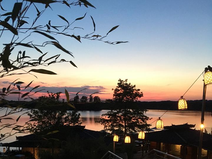 Blick ins Abendrot über den See aus der ersten Etage mit Laternen am Vabali Spa Düsseldorf